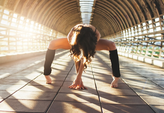 Slender young brunette woman street dancer gymnast sits in splits pose on street bridge Premium Photo