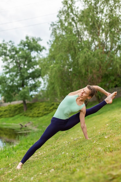 Slender young brunette yogi performs complex yoga exercise on green grass in summer Premium Photo