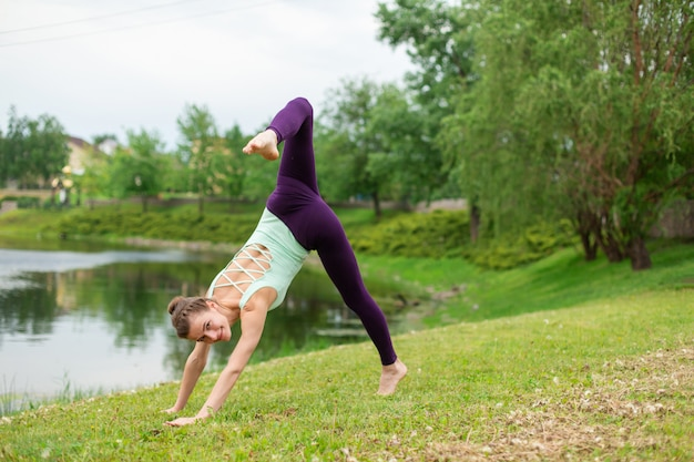Slender young brunette yogi performs complex yoga exercise on green grass in the summer Premium Photo