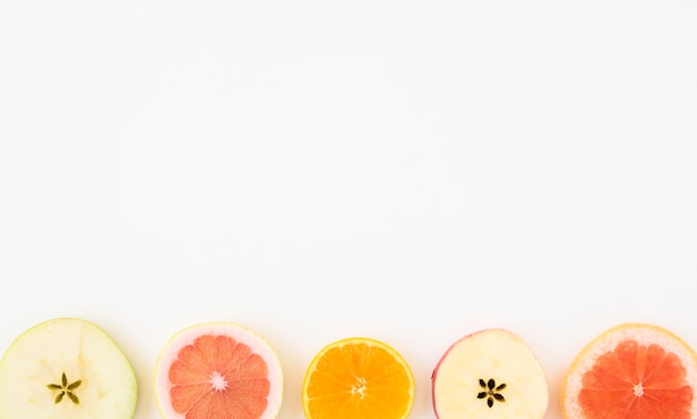 Slice of apple; grapefruit and orange slice isolated on whit backdrop with copy space for writing the text Free Photo
