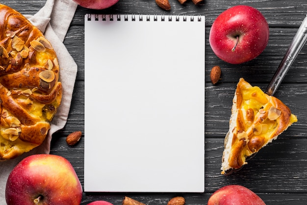 Slice of apple pie and empty copy space notepad Free Photo