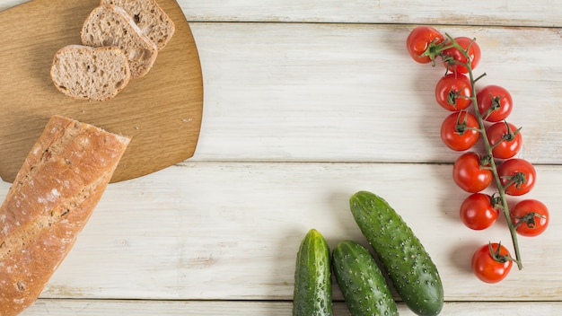 Slice of baguette; cucumber and cherry tomatoes on wooden desk Free Photo