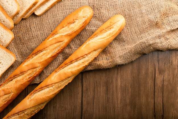 Slice of bread with baguette on tablecloth Free Photo