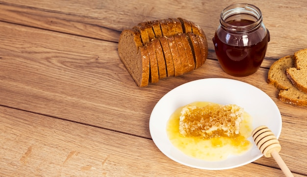 Slice of bread with honey and honeycomb on wooden texture backdrop Free Photo