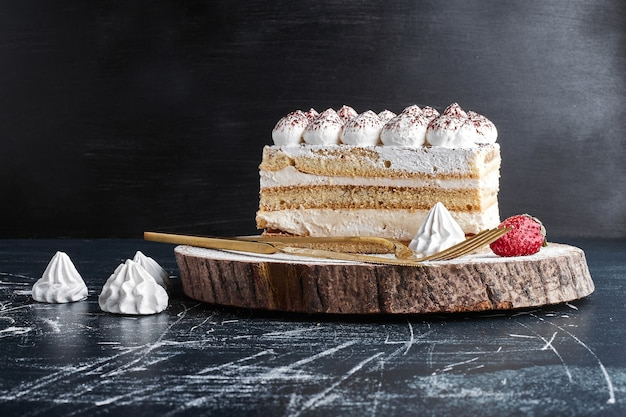 Una fetta di torta su una tavola di legno. Foto Gratuite