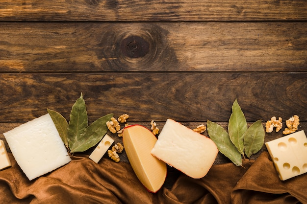 Slice of cheese; bay leaves and walnut arrange at bottom of the wooden background with silk material textile Free Photo