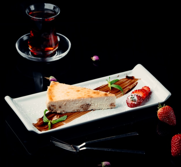 A slice of cheesecake with chocolate sauce,mint,strawberries and a glass of black tea. Free Photo
