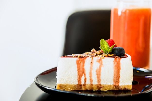 Slice of cheesecake with sauce and berries on black ceramic plate Free Photo