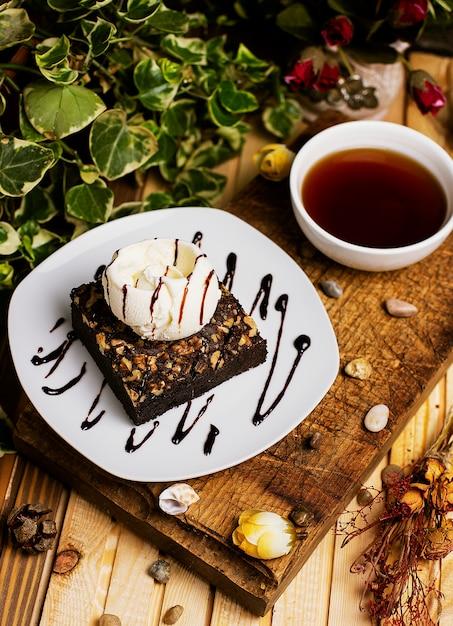 A slice of chocolate brownie with walnut and vanilla ice cream. Free Photo