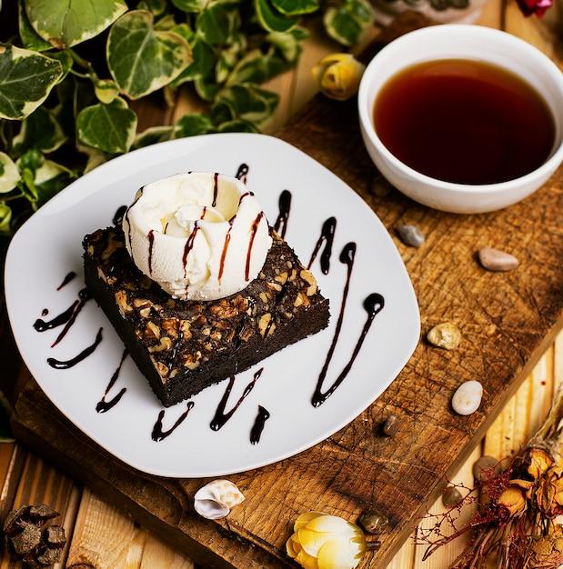 A slice of chocolate brownie with walnut and vanilla ice cream Free Photo