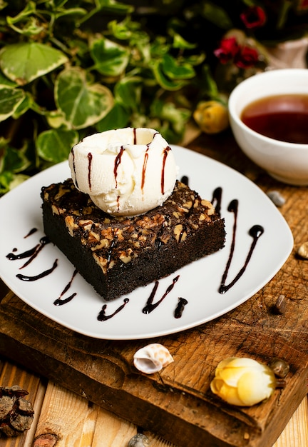 A slice of chocolate brownie with walnut and vanilla ice cream Free Photo