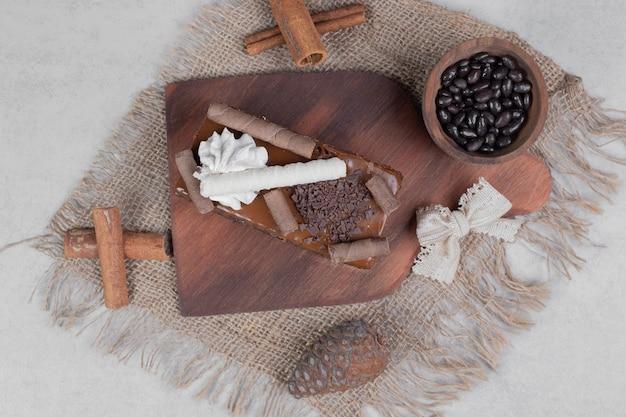 Fetta di torta al cioccolato, cannella e pigna su tela. foto di alta qualità Foto Gratuite