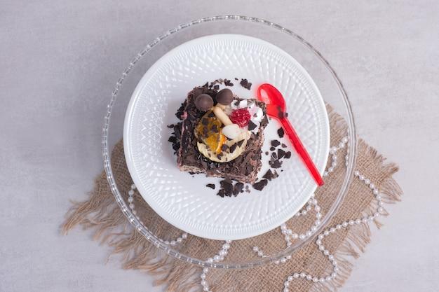 Fetta di torta al cioccolato sulla zolla bianca con perle. Foto Gratuite