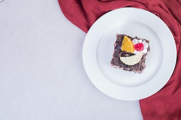 Fetta di torta al cioccolato sulla zolla bianca con tovaglia rossa. Foto Gratuite