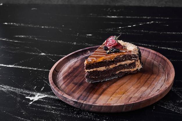 Una fetta di torta al caramello al cioccolato in un piatto di legno. Foto Gratuite