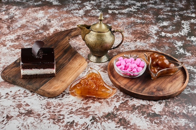 A slice of chocolate cheesecake with confiture and candies. Free Photo