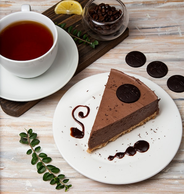A slice of chocolate mousse cheesecake with chocolate chips and a cup of tea. Free Photo