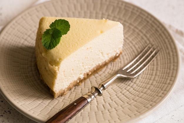 Slice of classical new york cheesecake on white plate. closeup view. home bakery Premium Photo