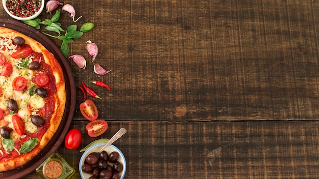 Slice of delicious pizza with ingredients on textured wooden background Free Photo
