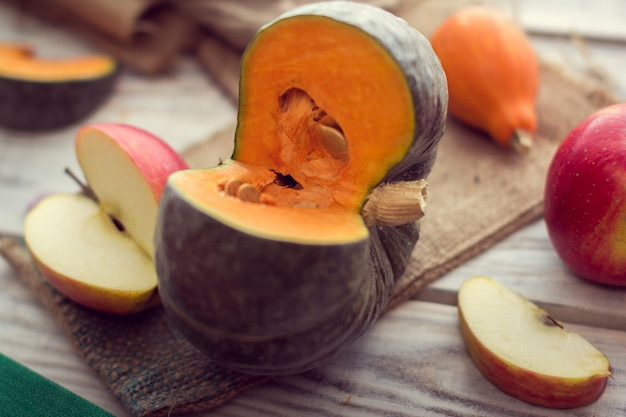 Slice of green pumpkin with slice of red apples Premium Photo