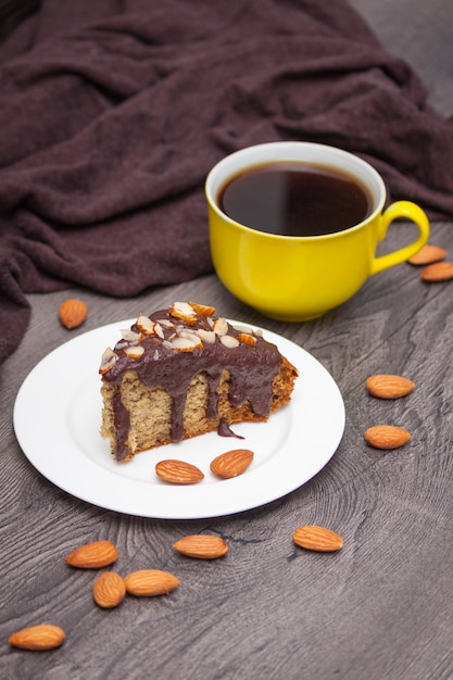 Slice of homemade banana bread with chocolate, almond and yellow cup of coffee on wood Premium Photo