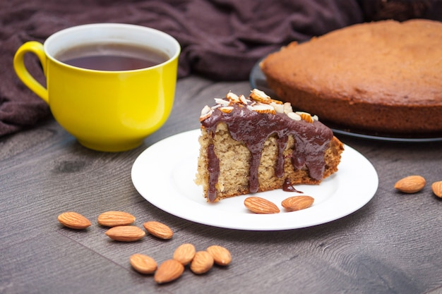 Slice of homemade banana bread with chocolate, almond and yellow cup of tea or coffee on wood Premium Photo