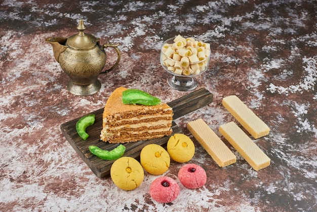 A slice of honey cake with butter cookies and waffles. Free Photo