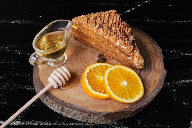 Una fetta di torta al miele con fette d'arancia e sciroppo d'acero Foto Gratuite