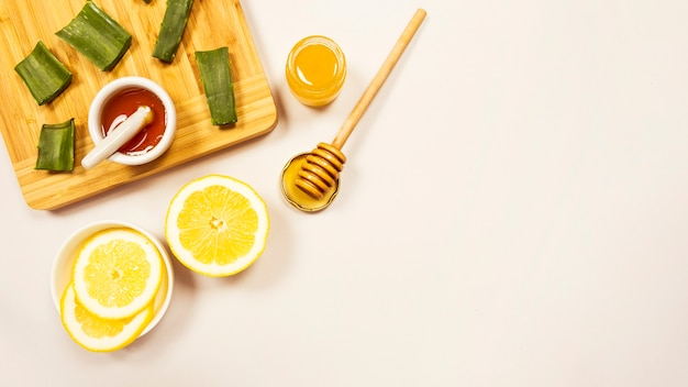 Slice of lemon and aloevera with honey over white backdrop Free Photo