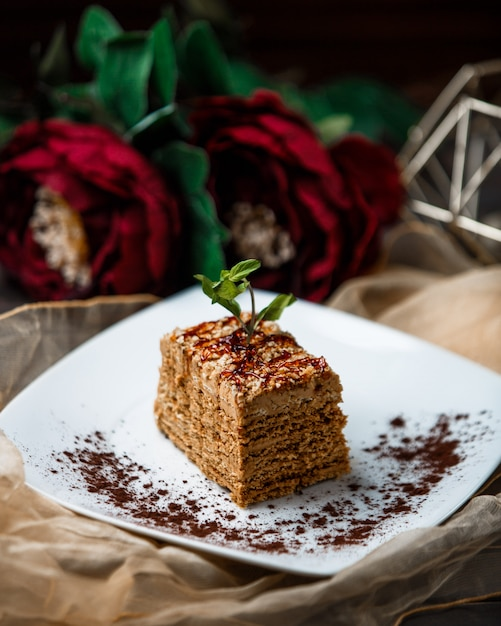 A slice of medovik cake with mint leaves. Free Photo