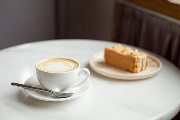 キャラメルケーキのスライスとホットコーヒーのカップ Premium写真