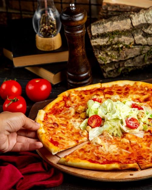 木の板にチキンとトマトのピザのスライス 無料写真