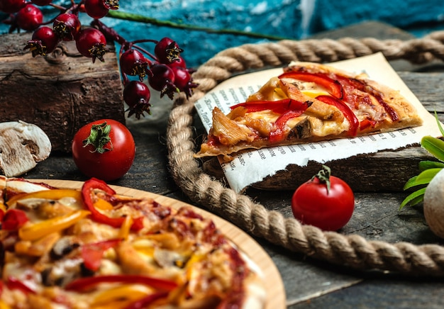 A slice of pizza and tomatoes on the table Free Photo