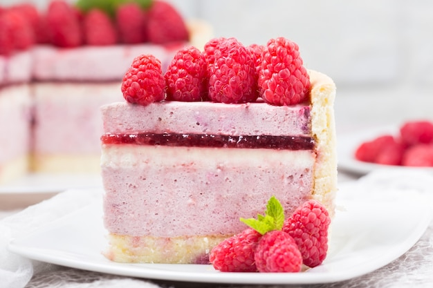 Slice of raspberry mousse cake with berry jelly and whipped cream Premium Photo