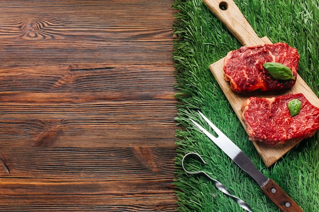 Slice of raw steak on wooden cutting board with metallic skewer and fork over grass mat Free Photo