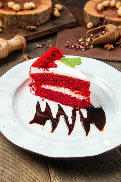 Slice of red velvet cake decorated with chocolate sauce Premium Photo