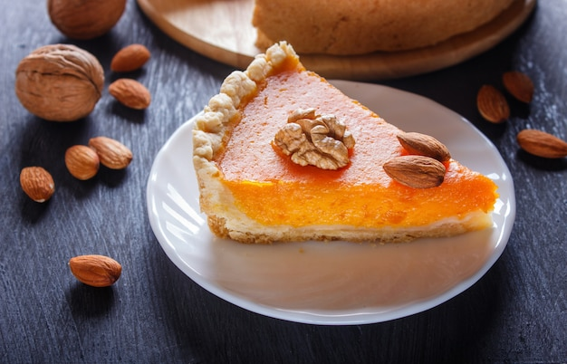 A slice of traditional american sweet pumpkin pie on black wooden surface. Premium Photo