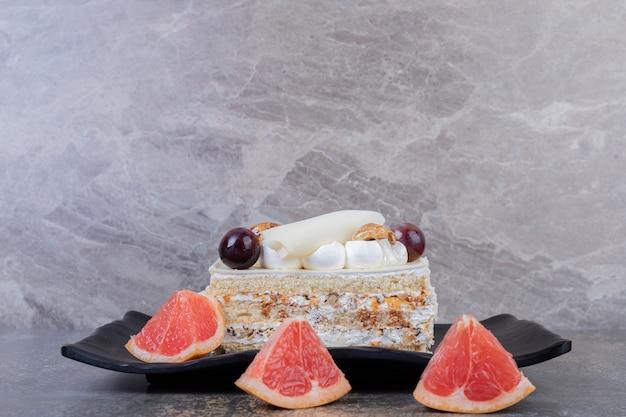 Fetta di torta bianca sulla piastra con fette di pompelmo. Foto Gratuite