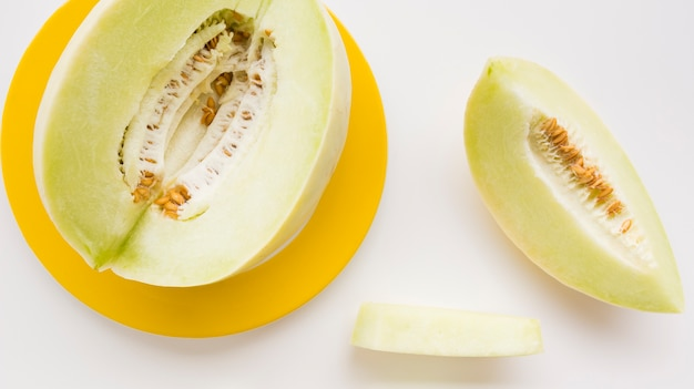 Slice and whole muskmelon on yellow plate over white backdrop Free Photo