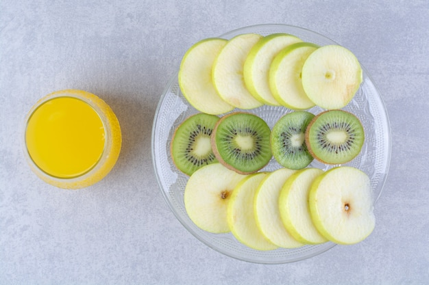 Sliced apple and kiwi on a glass pedestal next to a glass of orange juicy , on the marble table. Free Photo