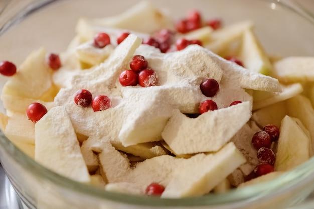 スライスしたリンゴとクランベリーをガラスのボウルに小麦粉を振りかけた。 Premium写真