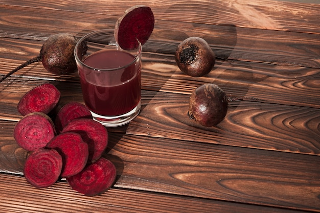Sliced beets and juice on wooden surface Free Photo