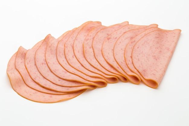 Sliced boiled ham sausage isolated on white background. Premium Photo