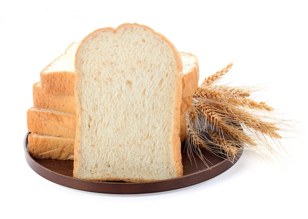 Sliced bread and wheat on wooden board isolated on white Premium Photo