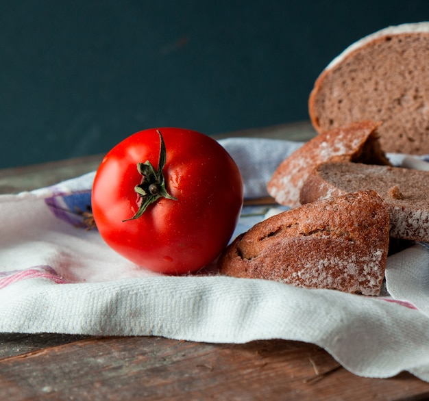 Sliced bread with a whole tomato on a white kitchen towel. Free Photo
