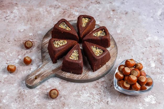 ヘーゼルナッツとスライスしたブラウニーケーキ。 無料写真