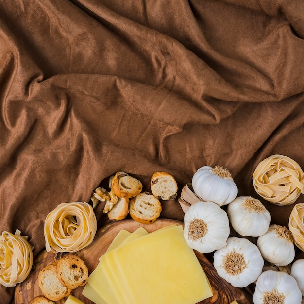Sliced cheese, raw pasta,  bread and garlic on brown cloth Free Photo
