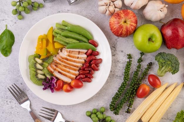 エンドウ豆、トマト、キウイ、カボチャとチキンステーキのスライス。 無料写真