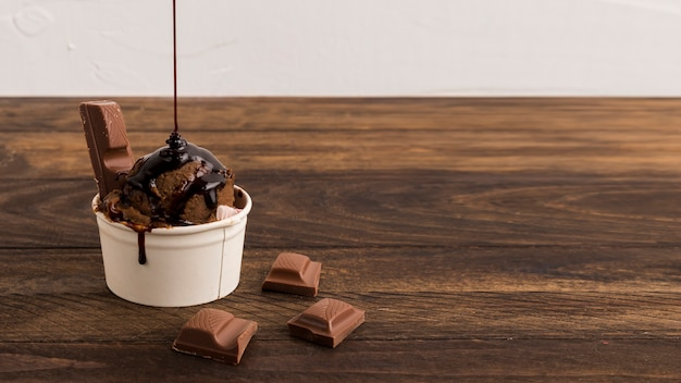 Sliced chocolate and ice cream with syrup in white bowl Free Photo