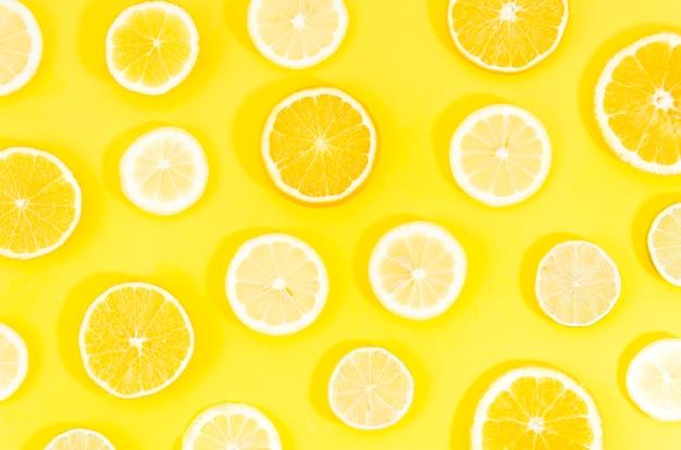 黄色の背景に柑橘系の果物をスライス Premium写真